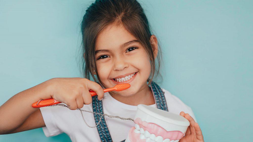 Mädchen putzt Zähne beim Kinderzahnarzt