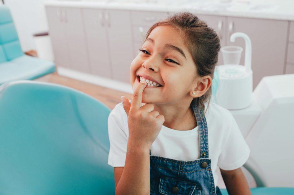 Mädchen zeigt ihre Zähne beim Kinderzahnarzt