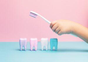 Kinderhand hält Zahnbürste über Modellzähne