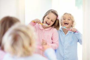 Kinder putzen sich lachend die Zähne