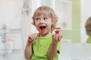 Kind putzt Zähne mit Sanduhr